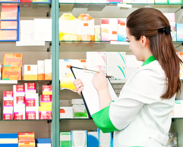 female pharmacist checking medicines in the shelves